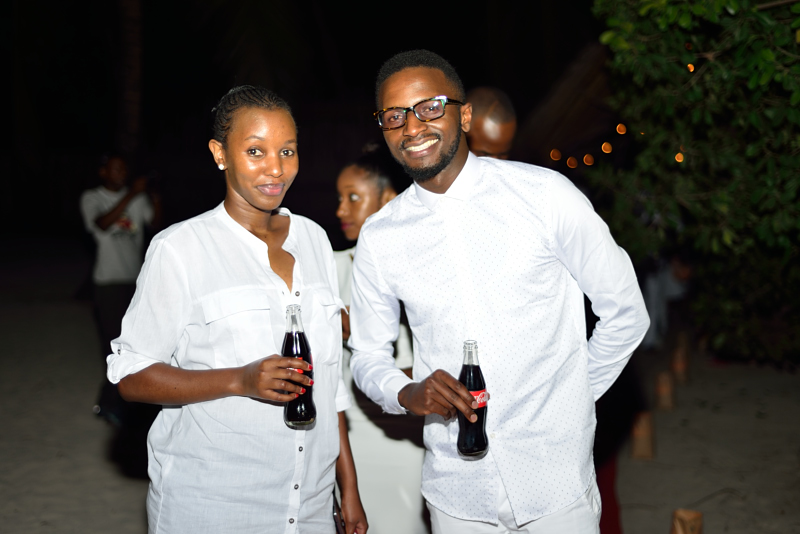 Caroline Spencer strikes a pose with Charles Wateba at the Vipingo Beach all white party during Coca-Cola's Taste The Feeling Launch